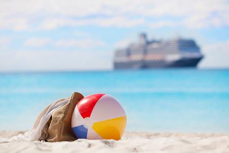 休暇の概念、ビーチボール、ビーチ バッグ バック グラウンドでクルーズ船が付いている砂のビュー