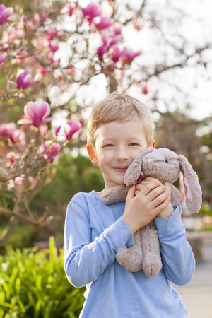 cute little boy with plush bunny toy at easter and spring time with blooming magnolia in the background photo