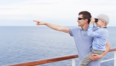 handsome young father holding his little son looking through binoculars, both enjoying cruise ship vacation together