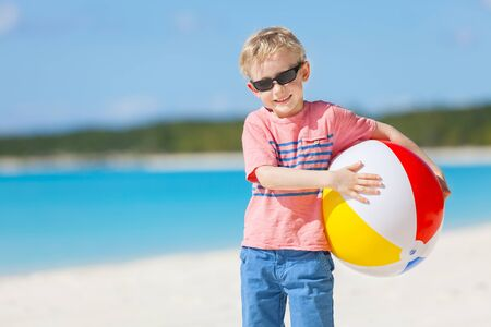 cheerful little boy holding colorful beach ball and having fun at tropical vacation photo