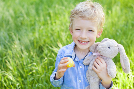 smiling cheerful little boy holding colorful easter egg and bunny toy at spring time in the park photo