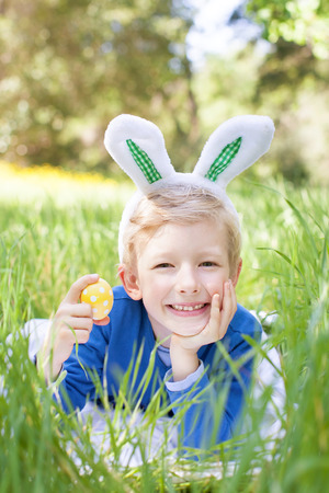 little smiling boy with bunny ears holding easter egg after egg hunt in the park lying in the grass photo