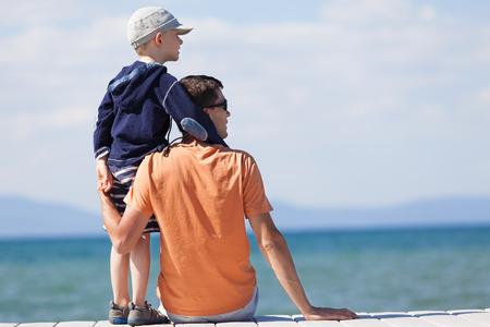 embrace family: familia de dos sentados en el muelle en el lago