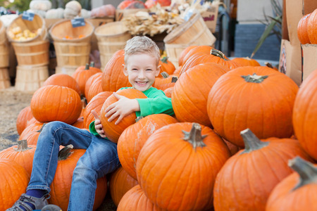 pumpkin patch: little excited kid enjoying time at pumpkin patch sitting in the huge pile of pumpkins