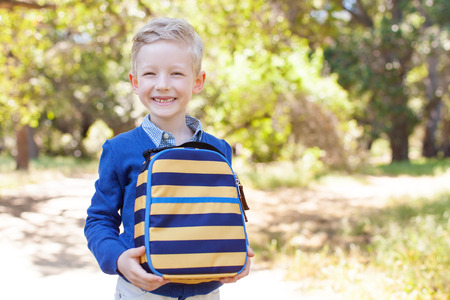 blue back: smiling little schoolboy holding lunchbag ready to go to school, back to school concept Stock Photo