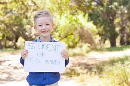 ni�os sosteniendo un cartel: sonriendo colegial poco dispuesto a ir a la escuela, de nuevo a concepto de la escuela
