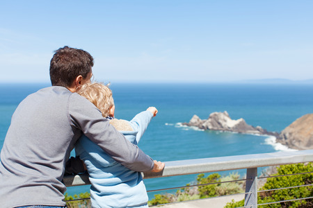 california coast: father and his son using binoculars together and enjoying the view of california coast Stock Photo