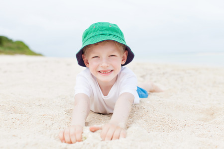 japan: little kid laying at the sand and enjoying day at the beach at taketomi island, okinawa, japan Stock Photo
