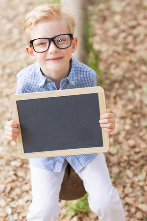 cool kids: little smiling boy in cute glasses holding empty chalkboard, back to school concept