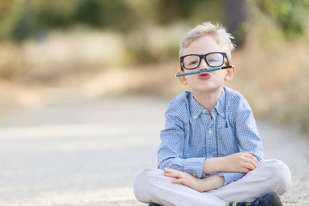 elementary school student: cute boy in glasses being silly, back to school concept Stock Photo