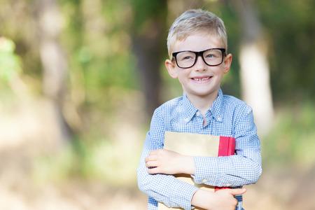 ni�os inteligentes: muchacho alegre en los vidrios que sostienen libro y prepararse para la escuela