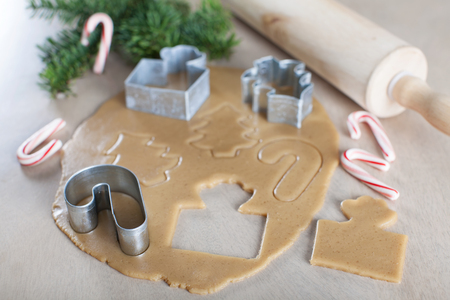rolled dough with christmas themed cookie cutters and rolling pin, candy canes and christmas tree branches in the background, christmas or new year time concept photo