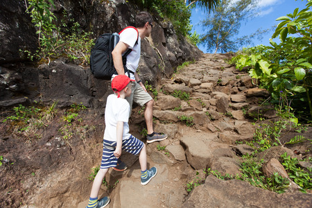 strenuous: family of two hiking up together the strenuous kalalau trail along nā pali coast of the island of kauai in the state of hawaii, spending active time together at vacation