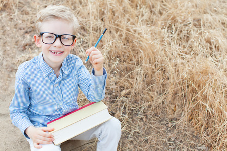 smart excited little boy in glasses studying with book and pencil ready for school, back to school concept