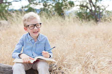 smart boy: smart excited little boy in glasses studying with book and pencil ready for school, back to school concept