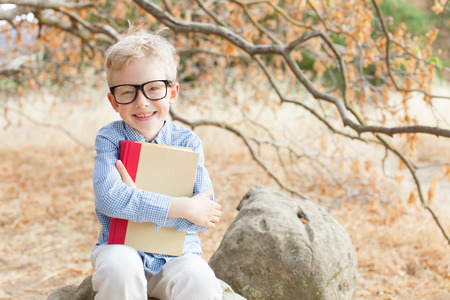 school children uniform: smart excited little boy in glasses studying with book ready for school, back to school concept