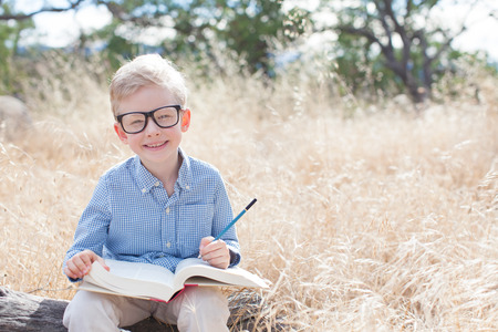 one little boy: smart excited little boy in glasses studying with book and pencil ready for school, back to school concept