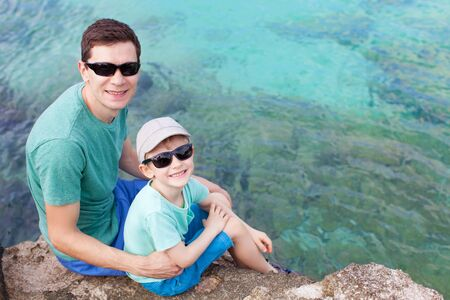 grand sons: family of two sitting at the rocky shore at cayman islands