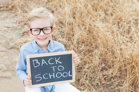 gafas: Ni�o peque�o emocionado inteligente en los vidrios que sostienen pizarra, listo para la escuela, de nuevo a concepto de la escuela