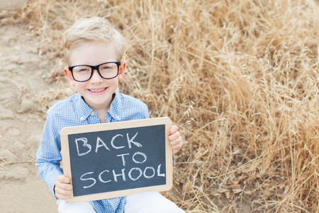 smart boy: smart excited little boy in glasses holding chalkboard, ready for school, back to school concept