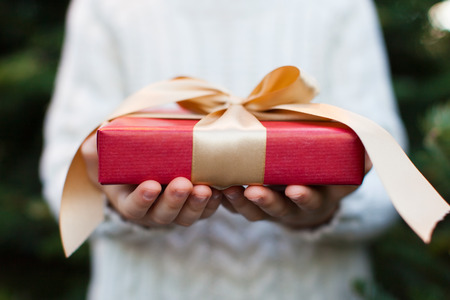 close-up of nicely wrapped christmas gift being held by a child with no face visible, christmas tree in the background, christmas time concept