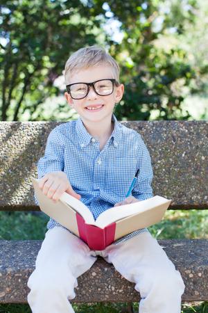 warm weather: smiling schoolboy in glasses studying ready for school enjoying warm weather in the park