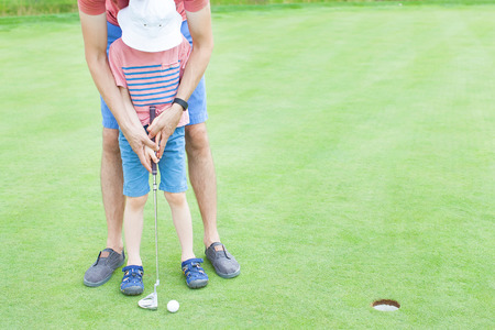 dad and child: young father teaching his little son to play golf, no faces visible Stock Photo