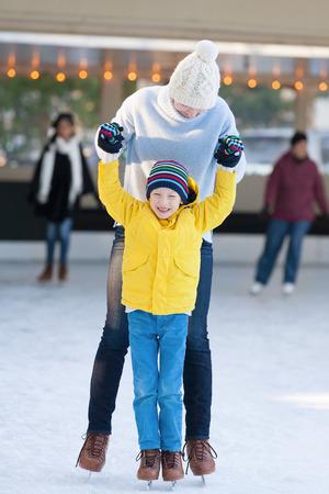 ni�o en patines: ni�o y su madre disfruta de clima fr�o del invierno y el patinaje sobre hielo en pista al aire libre Foto de archivo