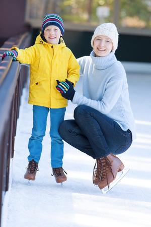 patinaje sobre hielo: joven madre que enseña a su hijo de patinaje sobre hielo positiva, disfrutar del tiempo de invierno en la pista de patinaje al aire libre juntos Foto de archivo