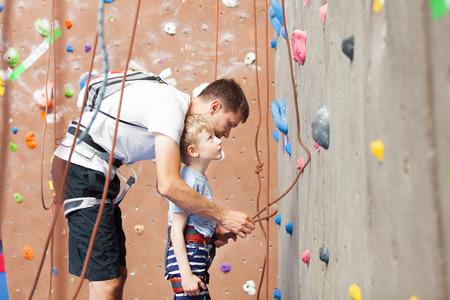 실내 체육관에서 등반을 위해 작은 아들을 준비하는 젊은 아버지 스톡 콘텐츠