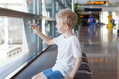 plane window: smiling caucasian boy playing with toy plane in the airport waiting for travel departure Stock Photo