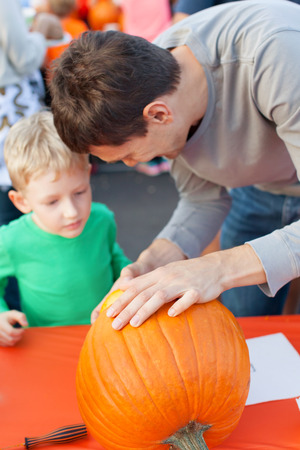 pumpkin carving: family of two enjoying pumpkin carving at halloween time