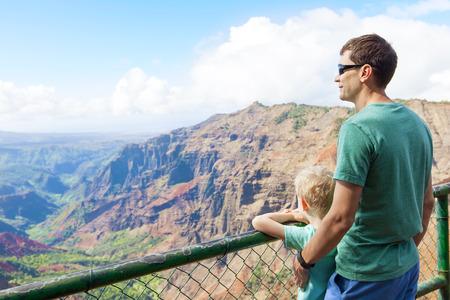 hawaii: family of two enjoying waimea canyon at viewpoint, kauai island, hawaii