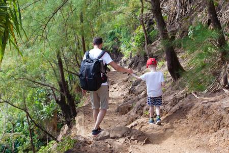 strenuous: family of two hiking together the kalalau trail at kauai island, hawaii