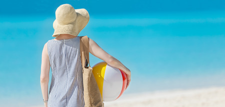 sunhat: back view of young woman in sunhat holding beach ball at beautiful caribbean beach