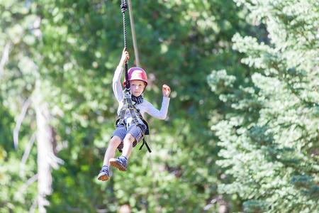 niño trepando: niño pequeño positivo tirolesa en el parque de aventura al aire libre copas de los árboles siendo activo y valiente Foto de archivo