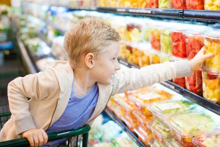 supermercado: positivo niño de 6 años de edad comprar frutas saludables en el supermercado o tienda de comestibles ayudando a sus padres Foto de archivo