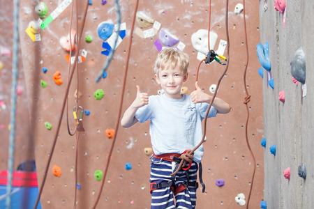 ni�o escalando: ni�o peque�o que da los pulgares para arriba en el gimnasio de escalada indoor Foto de archivo