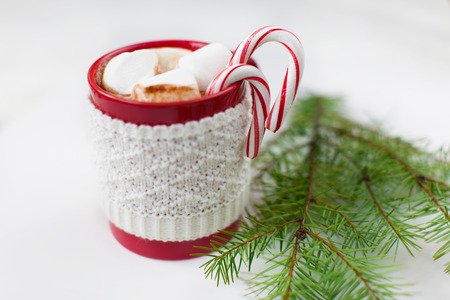 hot chocolate drink: cup with hot chocolate with marshmallows and candy canes - christmas time dessert and christmas tree branch Stock Photo