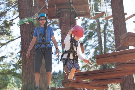 treetop: positive little boy and his father climbing at outdoor treetop adventure park being active and healthy together Stock Photo
