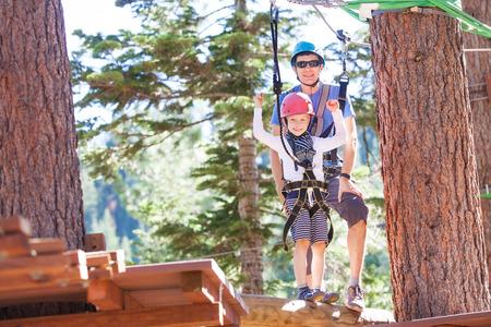 niño trepando: niño pequeño positivo y su escalada padre en los árboles al aire libre parque de aventura de ser activo y saludable juntos Foto de archivo