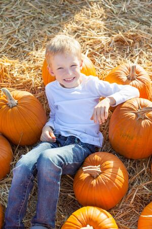 happy teenager: smiling 6-year old boy having fun and enjoying autumn time at pumpkin patch