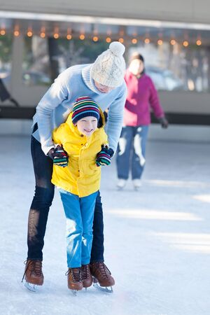 niño en patines: familia de dos personas a disfrutar el invierno patinaje sobre hielo en la pista de patinaje juntos al aire libre