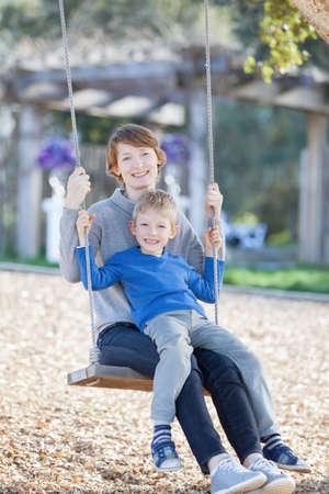 columpio: familia de dos personas disfrutando de tiempo juntos pivotar en el parque Foto de archivo