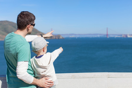 san francisco golden gate bridge: family of two enjoying the view of famous golden gate bridge and san francisco in california