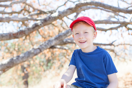 jungle boy: smiling 6-year old boy enjoying summer time in the forest climbing