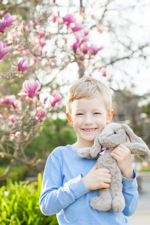 spring time: smiling cheerful boy holding easter bunny in the park with blooming trees enjoying spring time