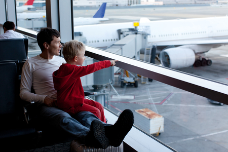 airport window: family of two at the airport enjoying time together before airplane departure
