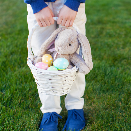 in the basket: little boy holding basket with colorful easter eggs and bunny in the park enjoying spring time, no face visible Stock Photo