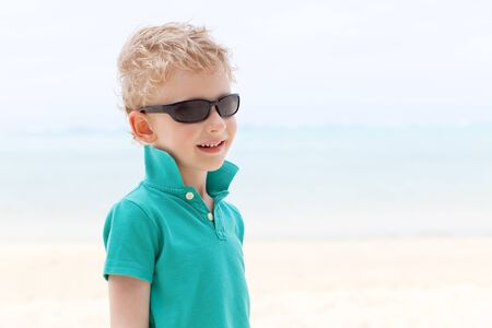 motu: portrait of handsome little boy in sunglasses at the beach